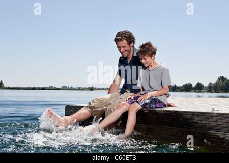 Vater und Sohn gemeinsam am Dock zu entspannen - Stockfoto