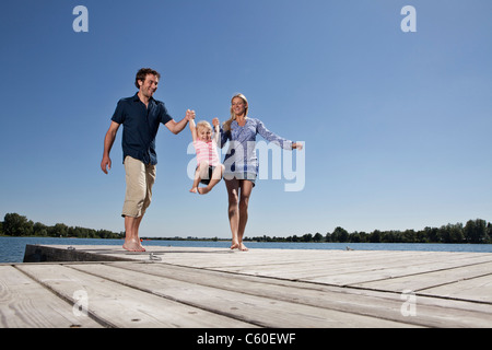 Eltern, die Tochter auf Dock schwingen - Stockfoto