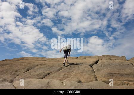 Eine 13-jährige geht Teenager auf steilen Sandsteinfelsen in der Küstenstadt Bucht von Trentishoe in North Devon. - Stockfoto
