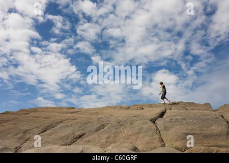 Ein 13 Jahre alter Teenager Spaziergänge die Spitzen der Sandsteinfelsen in der Küstenstadt Bucht von Trentishoe - Stockfoto