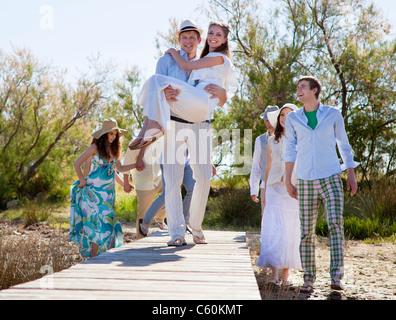 Bräutigam trägt Braut auf deck - Stockfoto