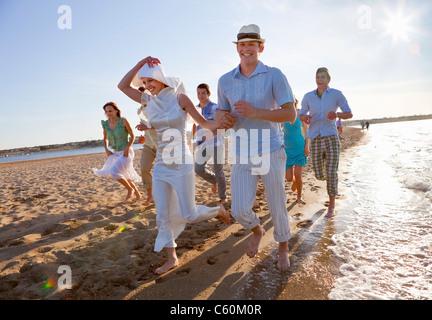 Frisch vermählte Paar am Strand mit Freunden - Stockfoto