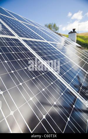 Solar Strom (Photovoltaik) und Solarthermie (Warmwasser) Panels auf einem Hausdach in Grasmere, Lake District, Großbritannien. - Stockfoto