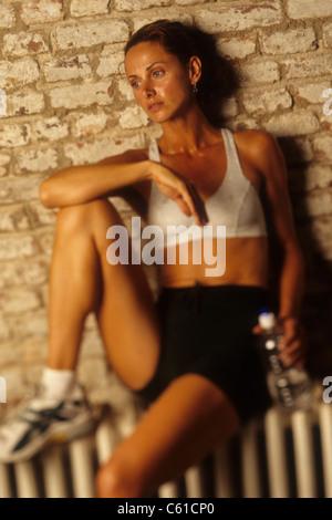 Frau, ausruhen und trinken nach dem Workout im Fitnessstudio. - Stockfoto