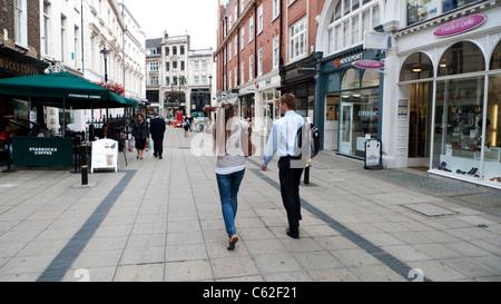 Ein junges Paar von hinten entlang vorbei an Geschäften und Boutiquen in der New Bond Street in London W1 England - Stockfoto