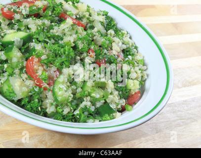 Quinoa-Tabouleh-Salat in einer Schüssel sitzt auf einem Holztisch. - Stockfoto