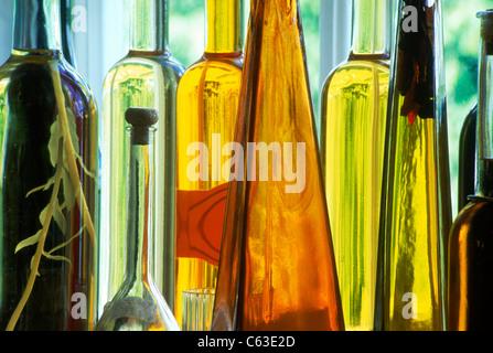Flaschen in verschiedenen Formen und Farben gefüllt mit Essig, Öle und gewürzte Flüssigkeiten sitzt auf der Fensterbank - Stockfoto