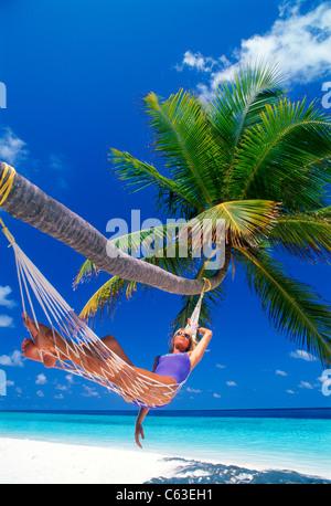 Frau mit Sonnenbrille zum Entspannen in der Hängematte unter Palme über weißen Sandstrand - Stockfoto