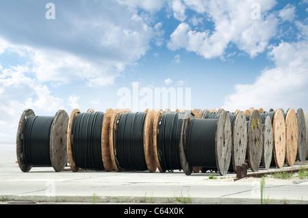 Große Rollen von schwarzen Kabeln auf blauen Himmelshintergrund - Stockfoto