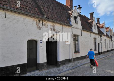 Weiße Armenhäuser entlang der gepflasterten Alley in Brügge, Belgien - Stockfoto