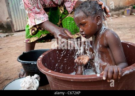 Eine Mutter taucht ihr Kind in einem Slum in Bamako, Mali, Westafrika. - Stockfoto