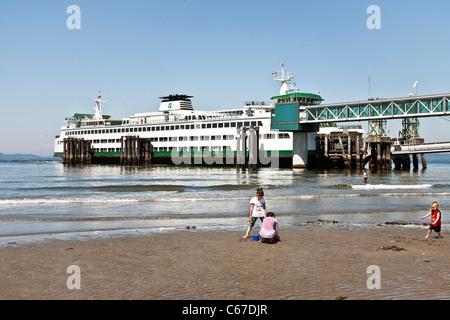 Kinder spielen gerne am Sandstrand neben Fähre Slip mit Washington State ferry Puyallup im Hafen von Edmonds, Washington - Stockfoto