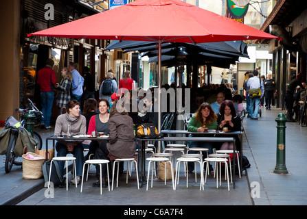 Menschen Sie sitzen und trinken Kaffee unter einem roten Markise in einem der berühmten Melbourne Gassen. Australien. - Stockfoto
