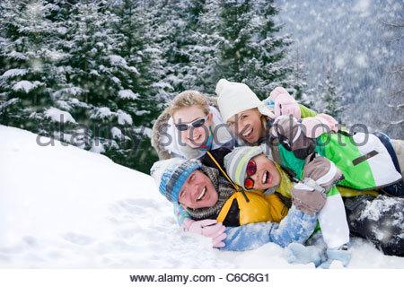 Porträt des Lächelns Familie Verlegung im Schnee - Stockfoto
