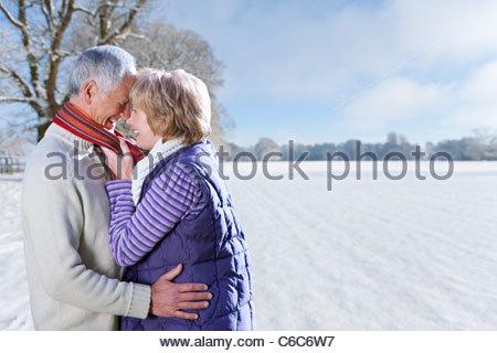 Älteres paar umarmt in sonnigen, verschneiten Feld lächelnd - Stockfoto