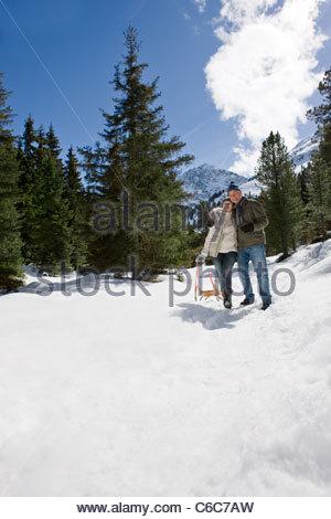 Älteres Paar mit Schlitten umarmt im verschneiten Wald - Stockfoto