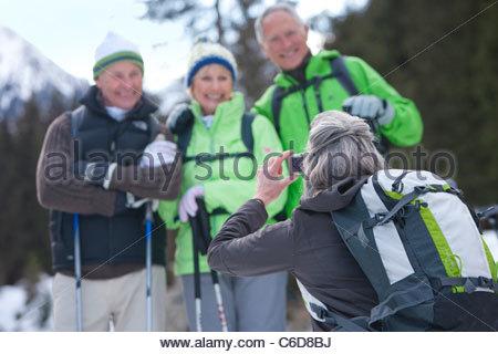 Frau nehmen Foto von Senioren Freunde im verschneiten Wald - Stockfoto