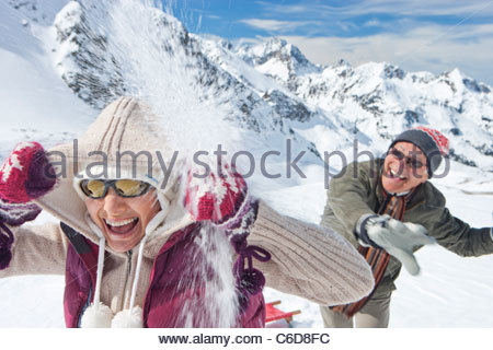 Spielerische älteres Paar im Schneeball kämpfen am Berg - Stockfoto