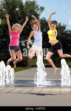 Drei junge Frauen, die in einen Brunnen springen - Stockfoto