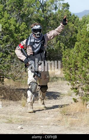 Paintball-Shooter durch einen Baum auf feindliche Stellung und Soldaten zu schießen. Zu anderen Teamkollegen Befehle - Stockfoto