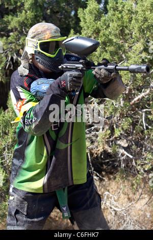 Paintball-Shooter hinter einem Baum auf feindliche Stellung und Soldaten zu schießen. Voller Schutz-Ausrüstung. - Stockfoto