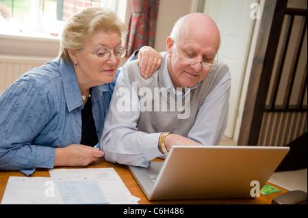 Älteres paar getrost bezahlen ihrer Rechnungen zusammen online - Stockfoto