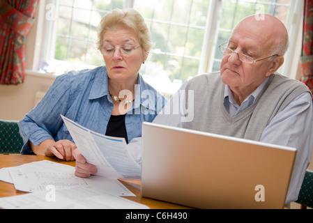 Älteres paar online durch ihre Rechnungen und Konten zusammen gehen - Stockfoto