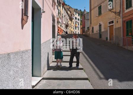Ein älteres italienisches Ehepaar Rede und Geste, wie sie Fuß auf dem Bürgersteig in ihrem Dorf Riomaggiore, Cinque Terre, Italien.