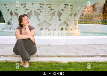 junge schöne Frau träumen vor Brunnen - Stockfoto