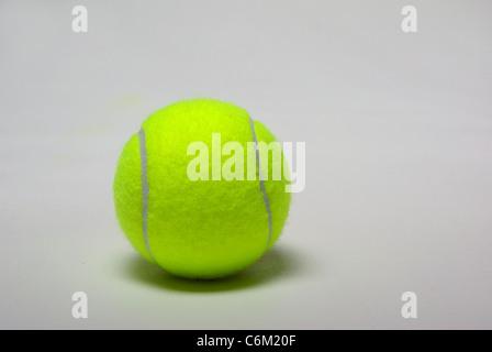 Ein grünen Tennisball sitzt auf einem weißen Hintergrund. - Stockfoto
