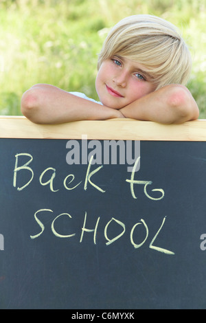 """Niedliche Schuljunge stand neben der Tafel mit dem Text """"back to School"""" - Stockfoto"""