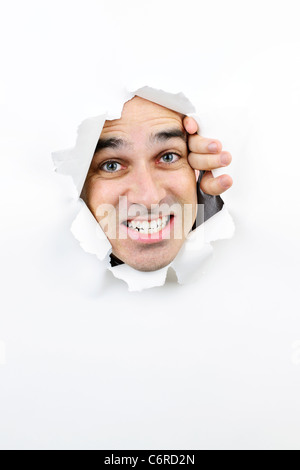 Loch im Papier mit zorniger Mann durchsehen - Stockfoto