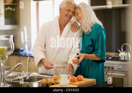 Älteres Ehepaar im Bademantel Kochen - Stockfoto
