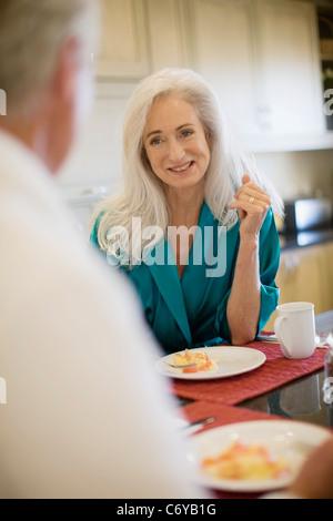 Älteres Ehepaar im Bademantel beim Frühstück - Stockfoto