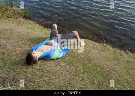 Teenager legen am Flussufer - Stockfoto