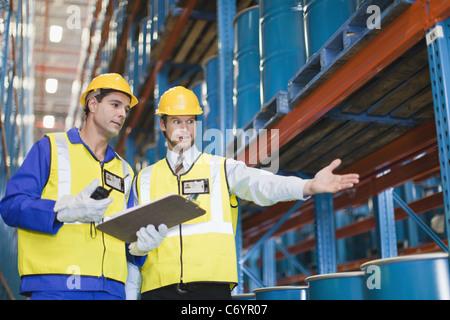 Arbeitnehmer mit Containern im Lager - Stockfoto