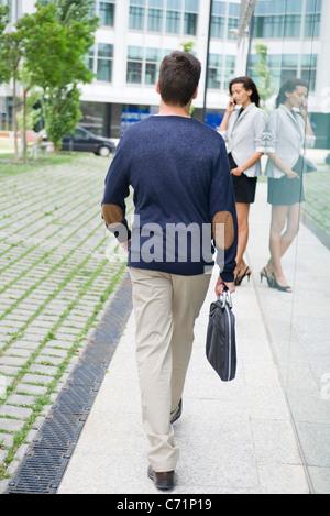 Mann mit Aktentasche, Frau am Handy im Hintergrund - Stockfoto