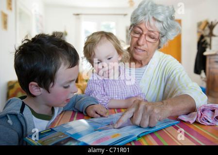 Großmutter Buch mit Enkelkinder - Stockfoto