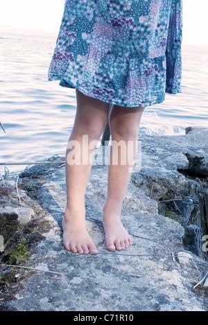 Kleines Mädchen im Kleid stehen auf Felsen von Wasser - Stockfoto