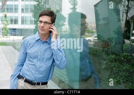 Mann in der Button-down Hemd Glaswand gelehnt, reden über Handy - Stockfoto