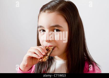 Mädchen essen Müsliriegel - Stockfoto