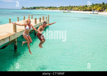 Eine Gruppe von Freunden springt aus Holz Dock in der kühlen Karibik - Stockfoto