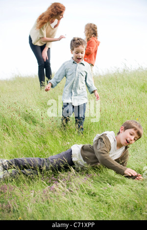 Jungs spielen in Feld, Mutter und Schwester im Hintergrund - Stockfoto