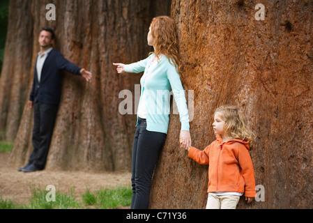 Eltern an verschiedenen Bäumen gelehnt Griff nach einander - Stockfoto