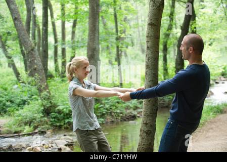 Paar halten Hände um Baum im Wald - Stockfoto