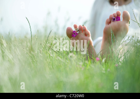 Barfuß junge Frau sitzt auf Wiese mit Wildblumen zwischen Zehen, beschnitten - Stockfoto