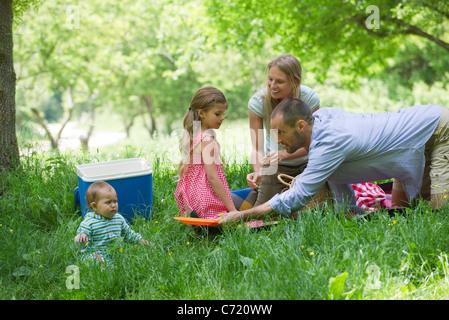 Familie mit Picknick auf Wiese - Stockfoto