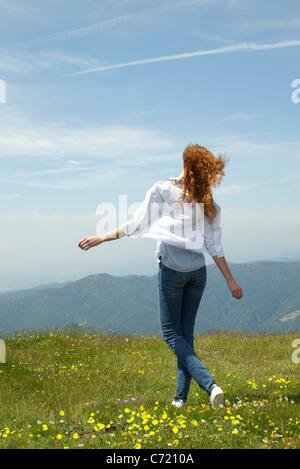 Frau zu Fuß durch Wiese mit ausgestreckten Armen - Stockfoto