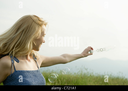 Junge Frau hält Blase Zauberstab im wind - Stockfoto