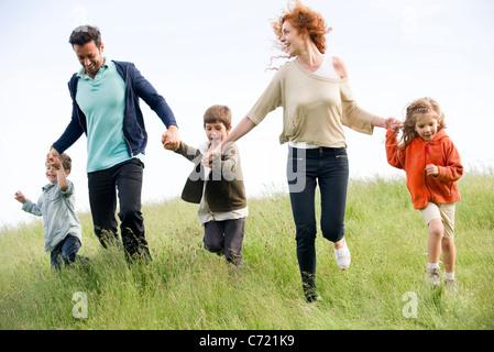 Familie laufen zusammen im Feld - Stockfoto
